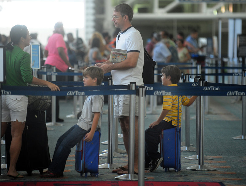 Twin brothers Liam, left, and Rowan Miller, 7, wait in line with their parents, Scott and Cynthia Miller, to board a flight in Ft. Lauderdale, Fla., last week. Families and friends who want to sit next to each other when they fly may have to pay extra as airlines try to sell roomier premium seats. Some airlines also no longer allow families with young children to pre-board.