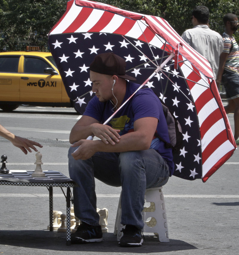 Luis Saavevra plays chess in New York's Union Square, with highs in the 90s.