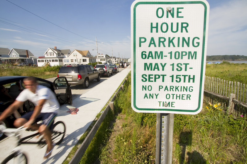 Parking on Bayview Avenue at Higgins Beach in Scarborough is allowed for free for one hour in designated spaces. Some residents want the town to require people to buy beach passes to park there.