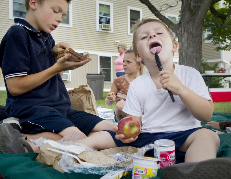 Mason Stoddard, 11, and Nickolas Keene, 3, picnic outside Little Falls Landing senior housing in Windham on Friday. This is the first summer that free lunches have been provided every weekday at the Windham site for children age 18 and under.