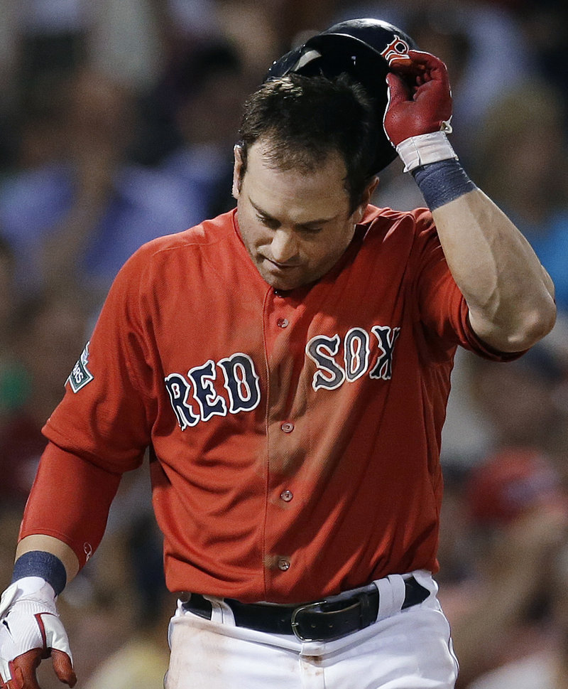 Nick Punto of the Red Sox heads back to the dugout after striking out with two on to end the seventh inning at Fenway Park.