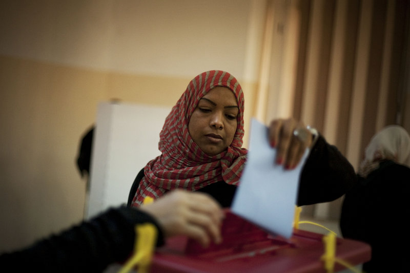 A Libyan woman votes at a polling station in the old city of Tripoli on Saturday. Voters flashed V-for-victory signs as they entered polling centers; motorists honked their horns.