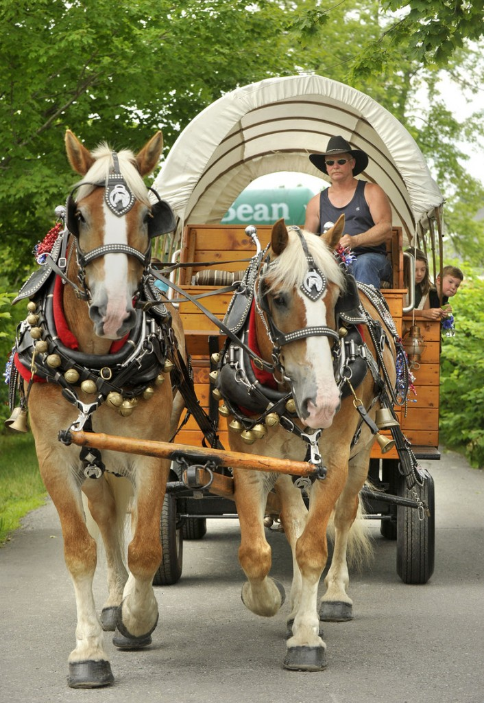 Visitors to L.L. Bean's celebration of its 100th anniversary in downtown Freeport ride on a horse-drawn wagon from Meadow Creek Farm on Saturday.