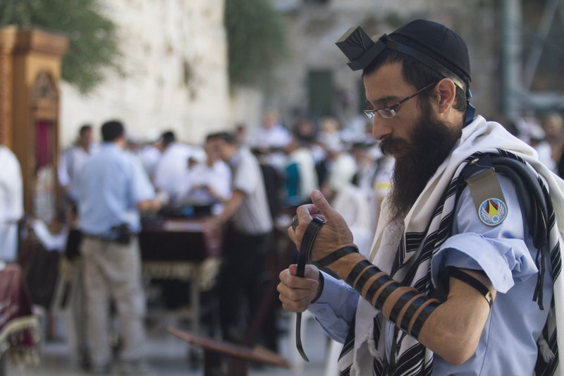 An Israeli soldier prays next to the Western Wall, the holiest site where Jews can pray, in Jerusalem. Secular males must perform three years of military service when they turn 18.