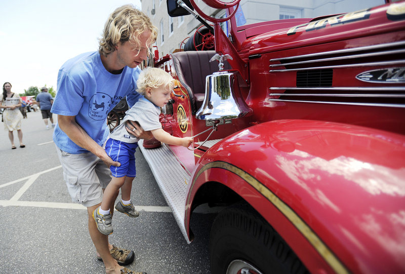 Isak Amundsen, 2, of Bath, with the help of his father Scott, rings the bell on a 1941 Bath fire truck on display at the antique car show on Sunday during Bath Heritage Days.