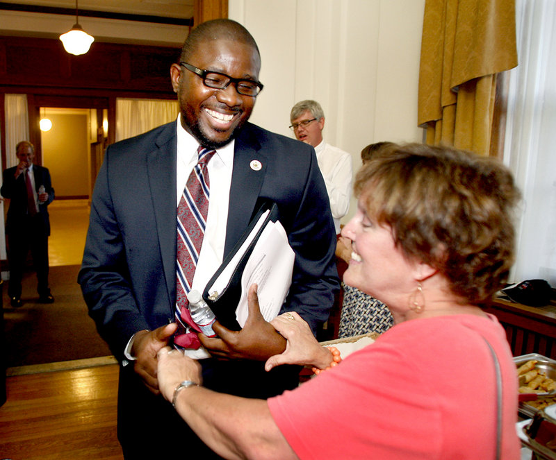 Emmanuel Caulk, the new superintendent of schools, chats with Longfellow Elementary teacher Joan Gildart at City Hall on Monday.