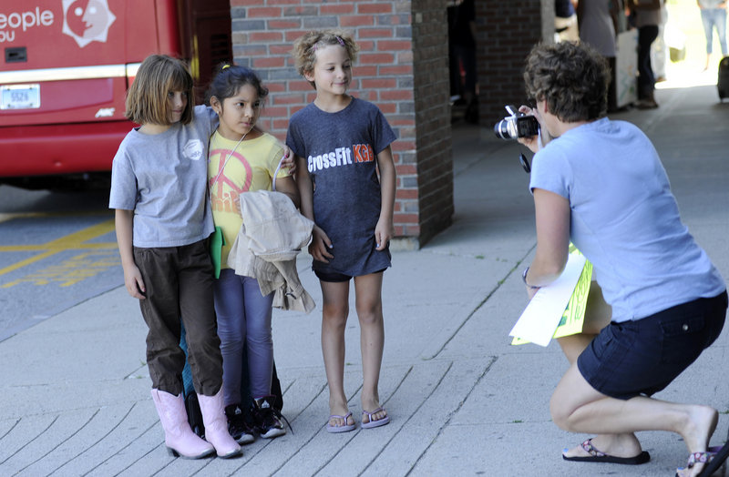 Cheri Poulin of Kennebunk takes a photograph of her daughters Lauren, left, and Katharine, right, both 8, as they pose with their visitor, Maria Castro 7, center, of New York City after Castro arrived in Kennebunk on Tuesday.