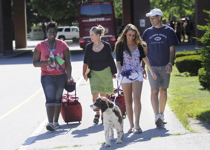 The Dube family – Sheila, Madi and Scott and their dog Baxter – of Dayton walk from the bus with their visitor, Jayla Reid, left. Reid is a returning visitor to Maine and the Dube home.