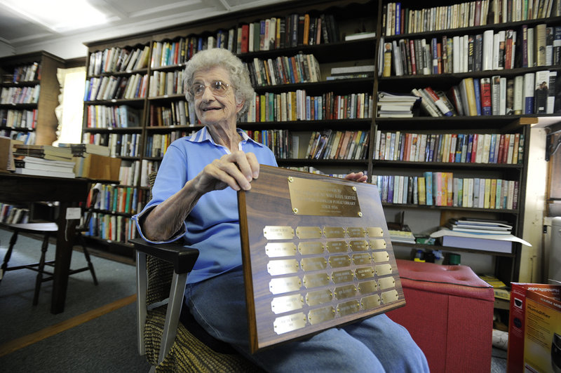 Librarian Lorraine Jonassen, 90, holds a plaque with the names of librarians who have served since 1934 at the South Windham Public Library on the Gorham/Windham line. The library is selling its remaining books and furnishings on Friday and Saturday.