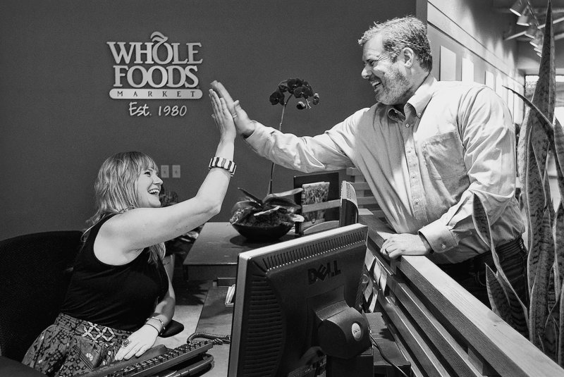 Whole Foods employees Mark Ehrnstein, global vice president for team member services, and Nikki Newman, a receptionist at the corporate headquarters, high-five one another in their Austin, Texas, office.