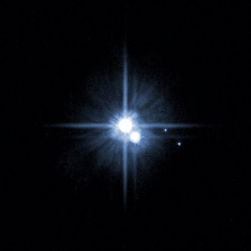 Pluto with three of its moons is shown in a picture taken from NASA's Hubble Space Telescope.
