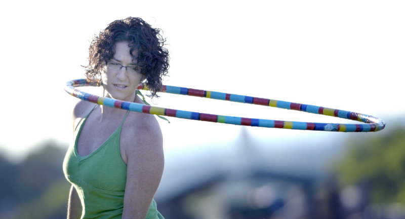 """Rachel Schwartz of Portland practices her hula-hoop skills Wednesday evening in a """"hoopla"""" run by Tracy Tingley. The free get-togethers occur weekly on the Eastern Prom in Portland; Schwartz said she participates """"because it's fun!"""""""