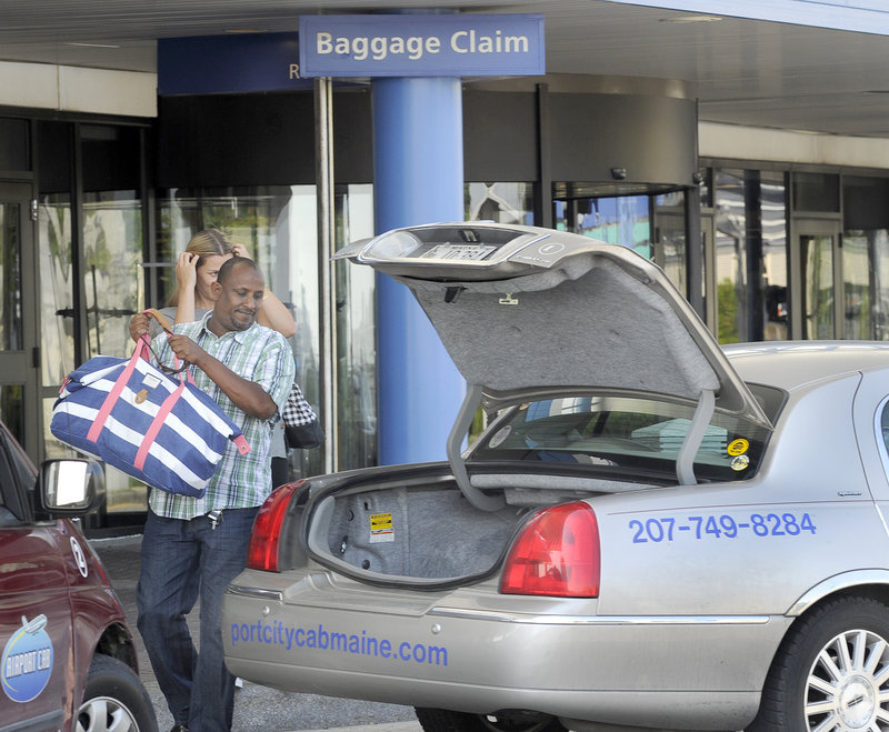 Taxi driver Rashid Olhaye handles the bag of a fare at the Portland International Jetport.
