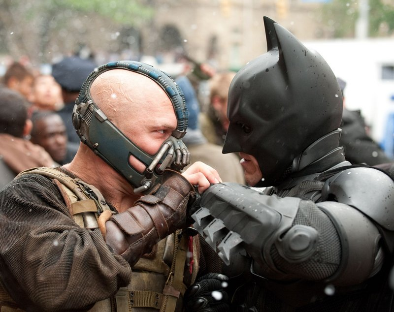 Tom Hardy plays Bane, left, a terrorist who attacks Gotham City and faces off with Batman.