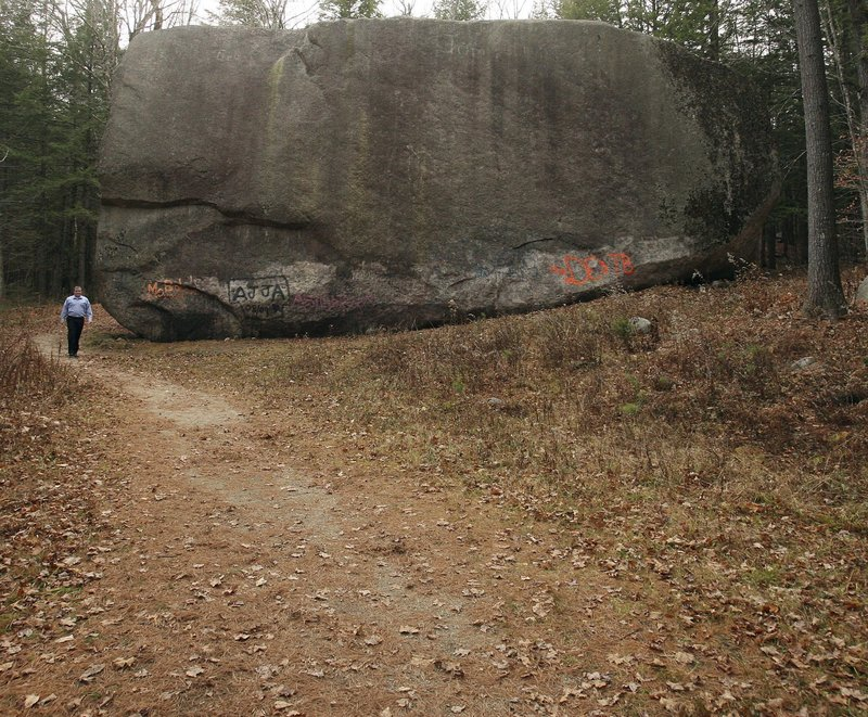 """The Madison Boulder towers over state Rep. Jeffrey St. Cyr as he walks a path at its Madison, N.H., site. The boulder is the largest-known glacial """"erratic"""" rock in New England, carried during the last ice age over mountains before breaking off here."""