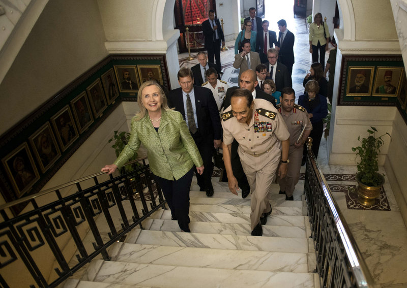 "Field Marshal Hussein Tantawi walks with U.S. Secretary of State Hillary Clinton on Sunday at the Ministry of Defense in Cairo. Clinton urged a return of Egypt's military to a ""purely national security role."" Tantawi replied that no one will distract the military from its purpose."