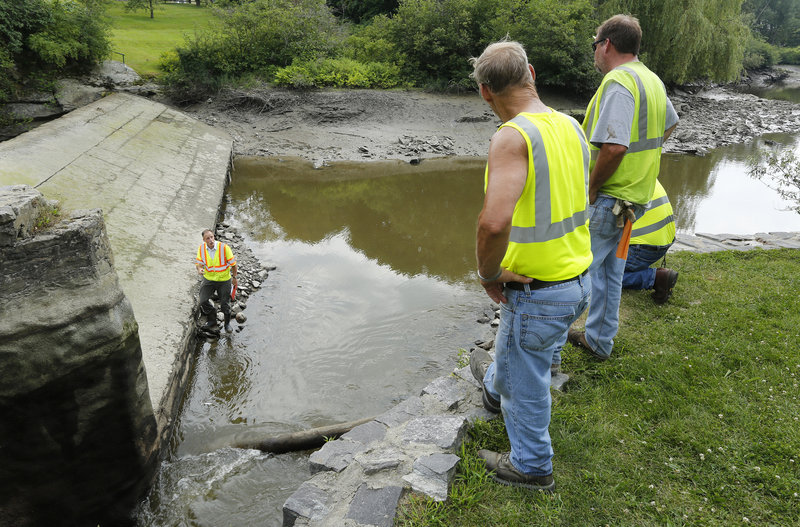 William Peterlein of Summit Geoengineering Services talks to city workers along the Stroudwater River after the water was lowered so the dam could be inspected. The upstream water level has been dropping, leading officials to suspect there is a leaky sluice gate.