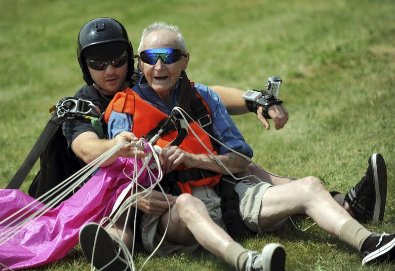 Ninety-year-old Lester Slate of Exeter sits on the ground Sunday after his first skydiving jump made in tandem with instructor Matt Riendeau, left, at Central Maine Skydiving in Pittsfield. The jump, witnessed by about 50 family and friends, was a birthday present to himself.