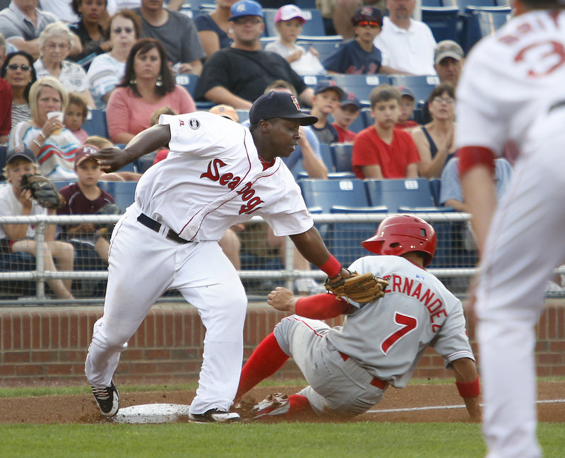 Marquez Smith of the Sea Dogs slaps on a tag too late on Reading's Cesar Hernandez in the first inning at Hadlock Field Monday night. Reading scored four times in the inning to win, 11-4.