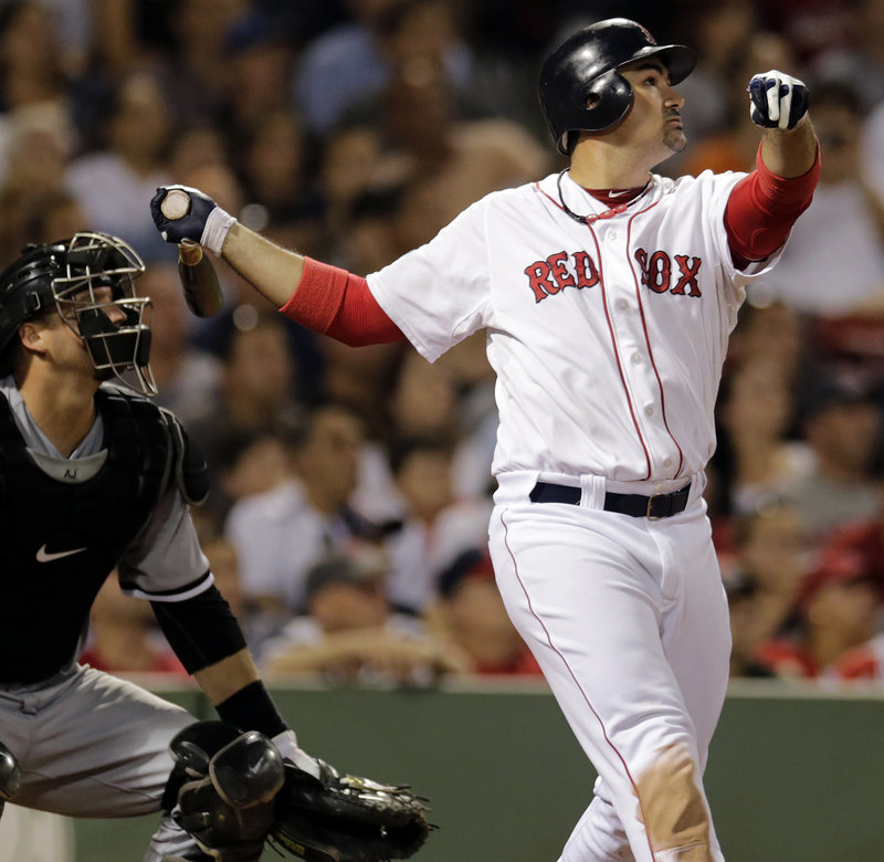 Adrien Gonzalez watches his three-run home run in the eighth inning of Boston's 5-1 win over the White Sox Monday at Fenway Park. Also watching is Chicago's A.J. Pierzynski.
