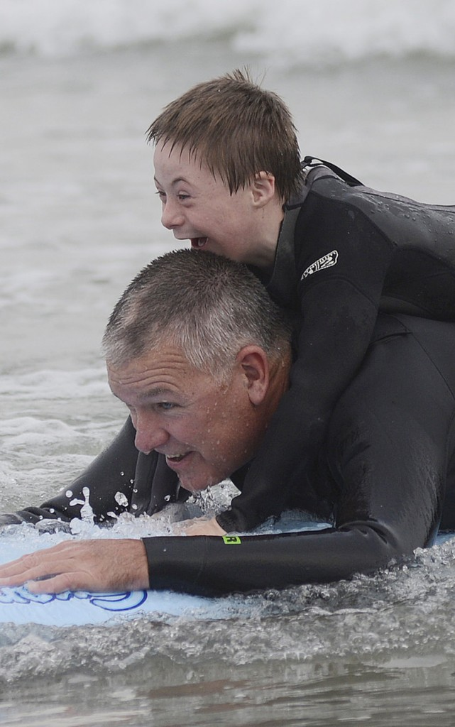 Eight-year-old Hunter Frechette of Biddeford is all smiles as he rides a wave on a surfboard while holding on to volunteer Marc Boutet of Saco during Special Surfer Night at Gooch's Beach in Kennebunk Tuesday.