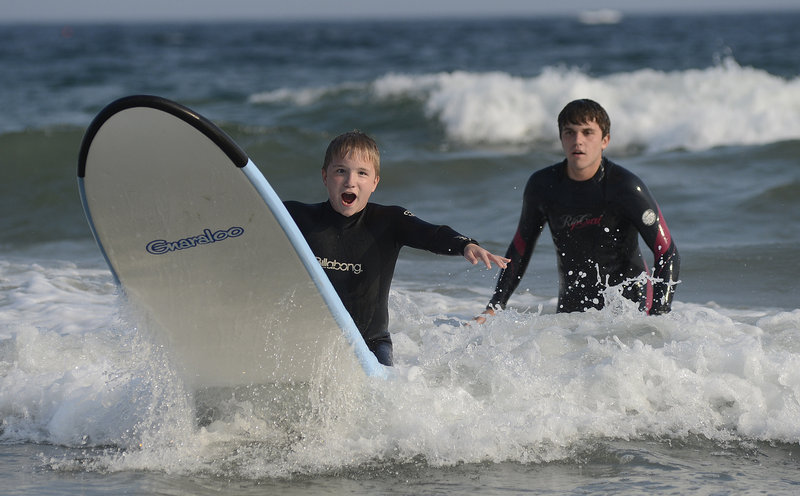 Noah Rassier, 12, of Milford, N.H., rides a wave with guidance from volunteer Daniel Gross of New York City.