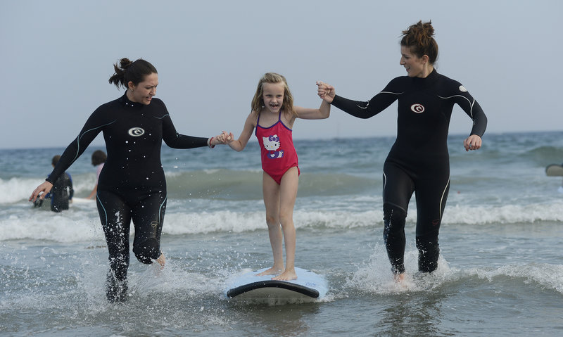 Seven-year-old Haley Adams of Standish gets an assist from volunteers Brittany Horwitz, left, of Vero Beach, Fla., and Jacky Marino of Denver.