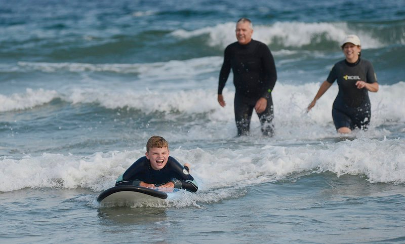 E.J. Marrifield, 9, of Belfast enjoys a ride on a surfboard during Special Surfers Night in Kennebunk on Tuesday. Looking on are volunteers Marc Boutet of Saco and Lynne Ableson of Kennebunk.