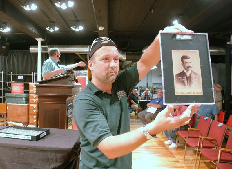 Don Hartford of Saco River Auctions holds up a baseball card of King Kelly of the 1888 Boston Beaneaters during an auction at tbe auction house in Biddeford on Wednesday evening. The card, which is only one of four known to exist in the world, sold for $62,000. Auctioneer Floyd Hartford conducts the bidding in the background.