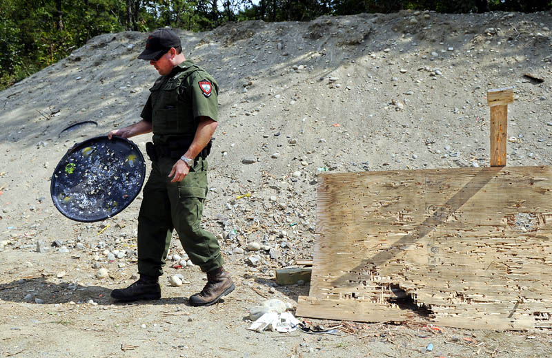 District Game Warden Steve Allaire collects garbage Thursday from the public target range on state land in the Summerhaven pits in Augusta. Allaire removes several hundred pounds of debris from the range each month.