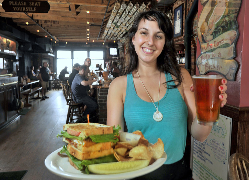 Server Michelle Blandina delivers a beer and a Chicken Stacker at Gritty McDuff's Portland location on Fore Street.