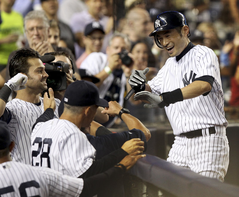 Ichiro Suzuki is greeted as he returns to the Yankees dugout after hitting his second home run of the game off Josh Beckett in a 4-1 victory Sunday night over the Red Sox.