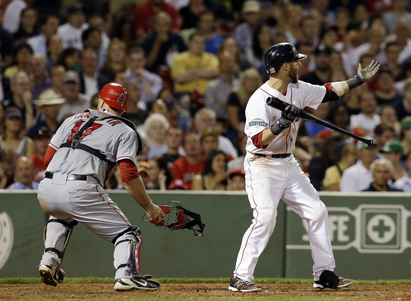 Dustin Pedroia of the Red Sox waves in Scott Podsednik, who scored from third on a wild pitch in the seventh inning as Angels catcher Chris Iannetta chases the ball.