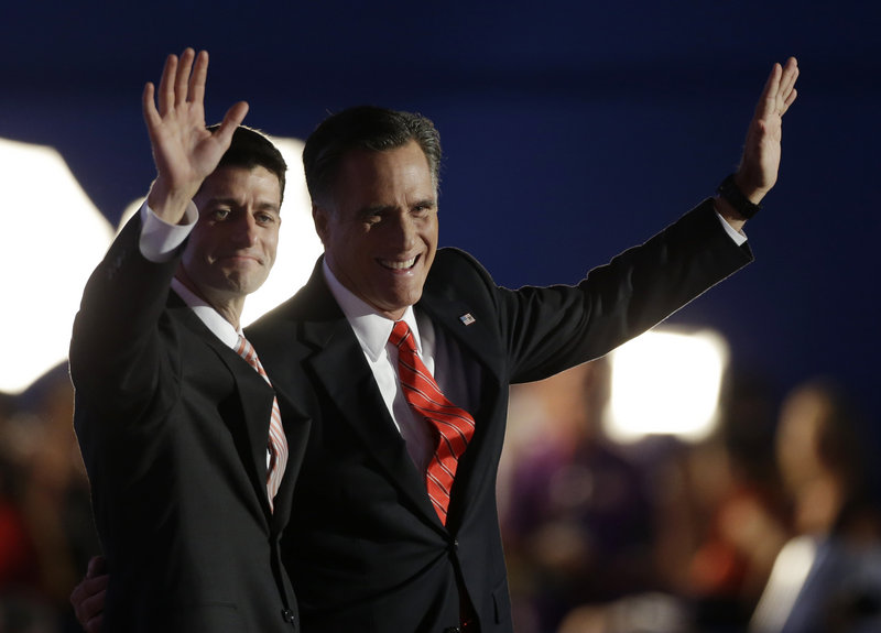 """Republican vice presidential nominee Paul Ryan, left, and presidential nominee Mitt Romney acknowledge the applause after Romney's speech. President Obama's promises """"gave way to disappointment and division. This isn't something we have to accept,"""" Romney said."""
