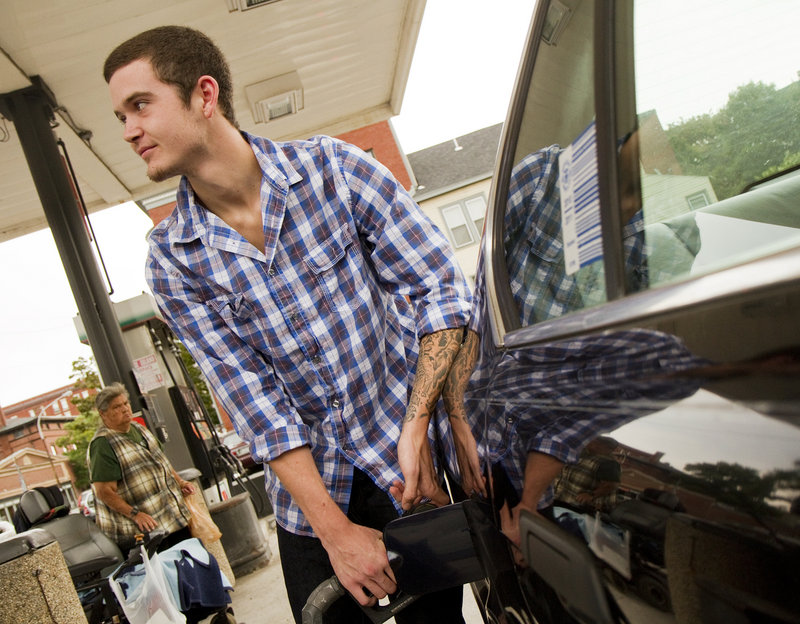"""Dylan McIntyre of West Falmouth fills up his 20-year-old BMW at a Congress Street gas station in Portland on Friday. """"I'm not too worried,"""" he said, shrugging off the price fluctuations even though he acknowledged that his car gets pretty abominable gas mileage."""