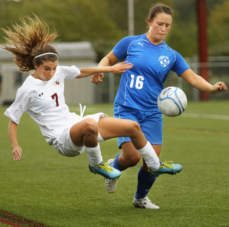 Kathryn Clark, left, of Cape Elizabeth lunges to get to the ball ahead of Falmouth's Bri DiPhilippo.