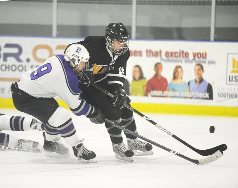 In this January 2010 file photo, former Deering High School player A.J. Asbury, No. 9, left, pressures the puck. Deering High School has received a waiver to merge its boys' hockey team with Portland High School's team.