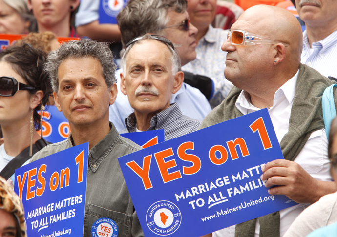 Dominic Rizzo, Nick McKenney and William Church, left to right, listen to a speaker on Monday during a rally at Portland City Hall held by Mainers United for Marriage.