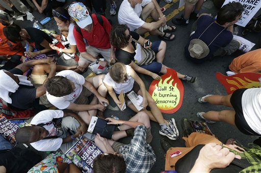 Demonstrators sit in an intersection during a protest march, Sunday, Sept. 2, 2012, in Charlotte, N.C. Demonstrators are protesting before the start of the Democratic National Convention. (AP Photo/Patrick Semansky)