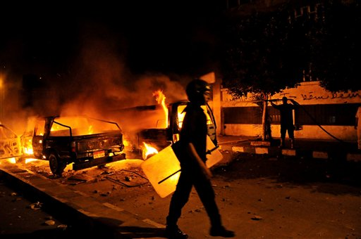 A riot policeman passes a burning vehicle during clashes outside the U.S. Embassy in Cairo, Egypt, early Thursday, as part of widespread anger across the Muslim world about a film ridiculing Islam's Prophet Muhammad.