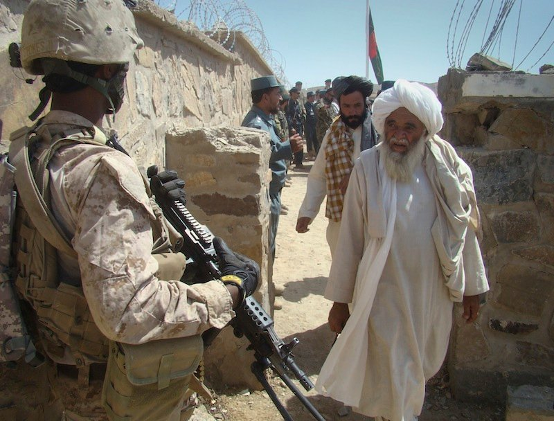 In this Saturday, Aug. 27, 2011 file photo, Afghan men, right, walk past a U.S. soldier to attend a meeting in Washer district, Helmand province, south of Kabul, Afghanistan. Helmand was the centerpiece of President Barack Obama's surge, when he ordered 33,000 additional U.S. troops to Afghanistan to help the military with a counterinsurgency plan. After nearly 12 years of military intervention, howeverm the country is not pacified. (AP Photo/Abdul Khaleq)