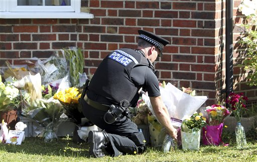 A police officer places flower tributes Saturday outside the Claygate, England, home of Saad al-Hilli, during investigations into the shooting deaths of al-Hilli, his wife and two other people Wednesday in the French Alps. The al-Hillis' 7-year-old daughter, Zaina, who was shot in the shoulder, came out of an induced coma Sunday but cannot yet talk to investigators. Her sister, Zeena, 4, escaped injury by hiding under her mother's skirt.