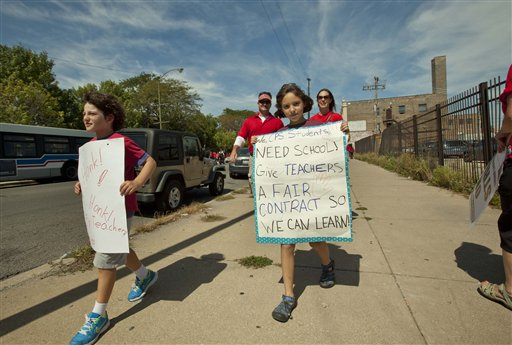 Children holding posters supporting striking teachers join a large group of public school teachers as they march on streets surrounding John Marshall Metropolitan High School on Wednesday in West Chicago.