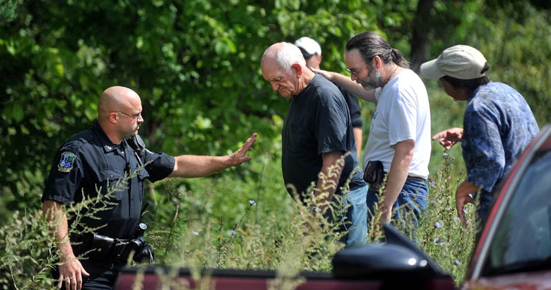 Waterville police officer Steve Brame, left, gestures for Horace Crawford, center, to wait on the road for paramedics. John McCuthon, center right, comforts Crawford. McCutchon was traveling in the opposite direction and witnessed Crawford go off the road.