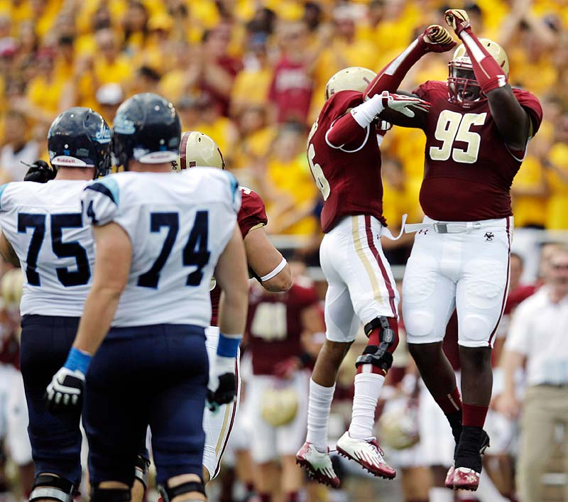 Boston College defensive lineman Dominic Appiah, 95, celebrates with C.J. Jones, 6, after the Maine fumbled on a punt near the Boston College end zone in the first half Saturday at Alumni Stadium in Chestnut Hill, Mass. At left are Maine's Joe Hook, 75, and Josh Spearin, 74.