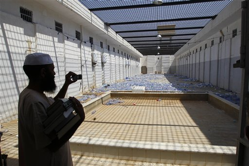 A Libyan man takes pictures of the courtyard of Abu Salim prison, in Tripoli, Libya. in this 2011 photo.