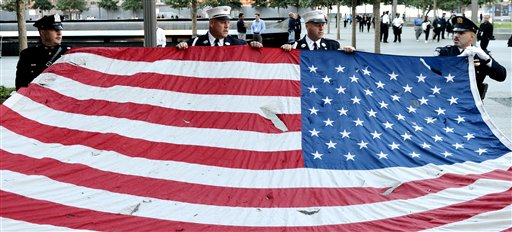 Police officers of the Port Authority of New York and New Jersey, carry an American flag that flew over at the World Trade Center towers, during the 11th anniversary ceremonies at the site of the World Trade Center, in New York, Tuesday Sept. 11, 2012. The Associated Press photo