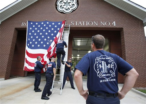 Capt. Kris Small of the Rock Hill, S.C., Fire Department watches as other firefighters put a giant American Flag on the front of Station 4 on Tuesday to commemorate Sept. 11 terrorist attacks.