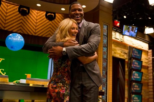 Former football player Michael Strahan, right, embraces Kelly Ripa on the set of the newly named