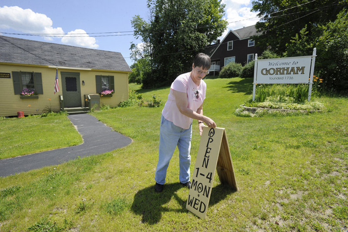 In this July 11, 2012, photo, Ellen Bessey, daughter of former librarian Lorraine Jonassen, sets out the open sign for the last time before the closing of the South Windham Library due to lack of customers.